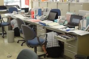 館内放送が流れ、素早く机の下に身を隠す職員