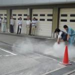 消火器の正しい操作方法を聞き、一気に消火する参加者。
