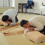 マネキンを使って、気道を確保し、人工呼吸の訓練をする参加者。
